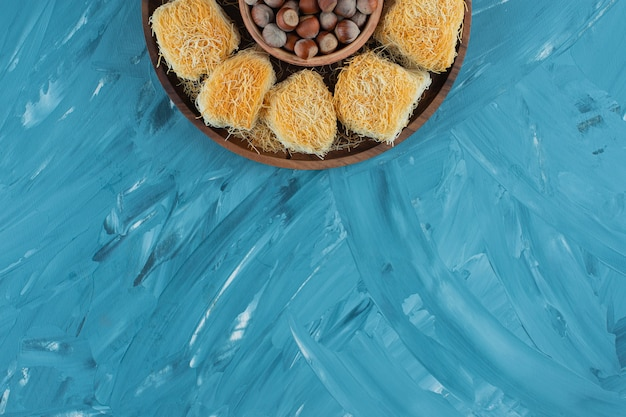 Turkse lekkernijen met macadamia noten op een donkere houten plaat.