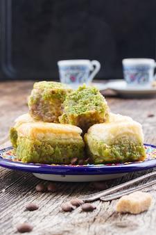 Turkse lekkernijen. plaat van baklava-snoepjes met kopjes koffie