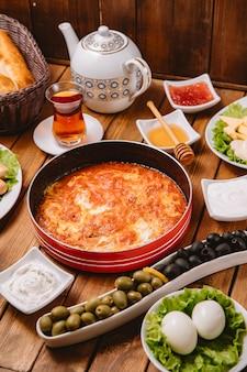 Turkse ontbijtopstelling met ei en tomatenschotel, worst, olijven, eieren en thee