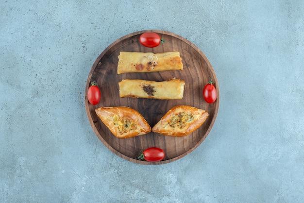 Turkse pide en russische blins op een klein dienblad op marmeren oppervlak