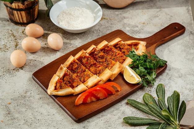 Turkse pide geserveerd met tomaten, peterselie en citroen