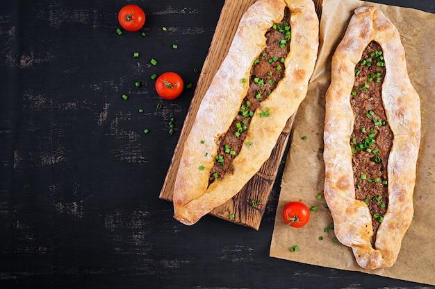 Turkse pide met gehakt, kiymali pide. traditionele turkse keuken. turkse pizza pita met vlees. bovenaanzicht, boven het hoofd