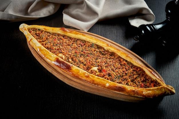 Turkse pide met lamsgehakt, tomaten, paprika op een zwarte tafel