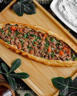 Turkse pide pizza met vlees en plantaardige vulling in houten dienblad.
