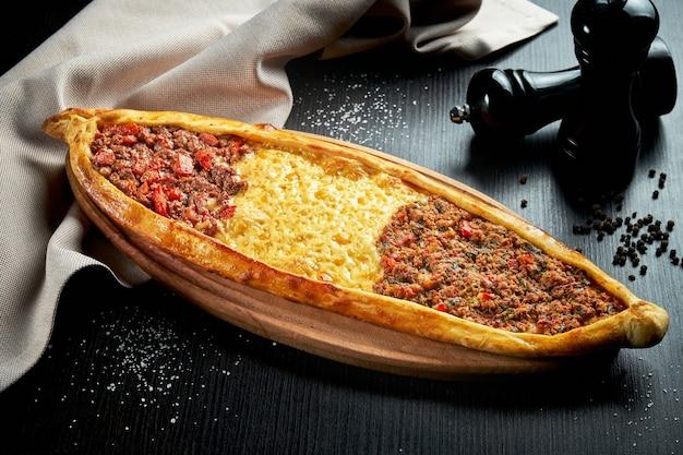 Turkse pide schotel met drie verschillende vullingen: lamsvlees, rundvlees en cheddar kaas op een zwarte tafel. close-up, selectieve aandacht