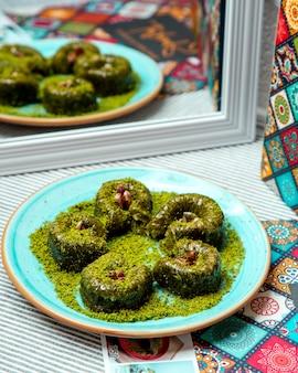 Turkse sarma met pistache op een blauwe plaat