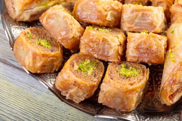 Turkse snoepjesbaklava en metaal oosters dienblad op houten achtergrond