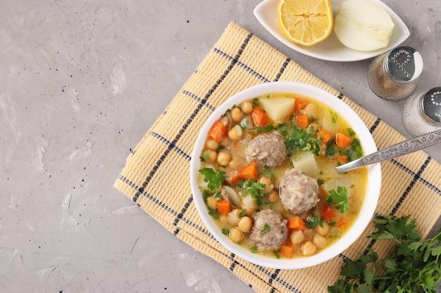 Turkse soep met kikkererwten, gehaktballen en groenten in een witte kom op een grijze ondergrond. met plaats voor tekst. bovenaanzicht