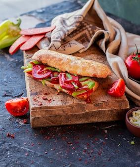 Turkse sucuk ekmek in stokbrood op een houten tafel.