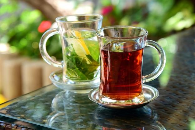 Turkse thee en muntthee met citroen in glazen bekers op glazen tafel