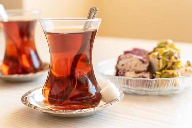 Turkse thee in een traditioneel glas staat op de tafel close-up