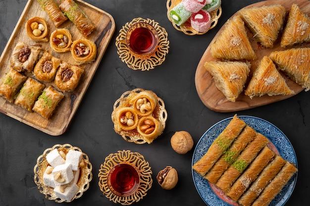 Turkse thee in traditionele glazen baklava op zwarte achtergrond