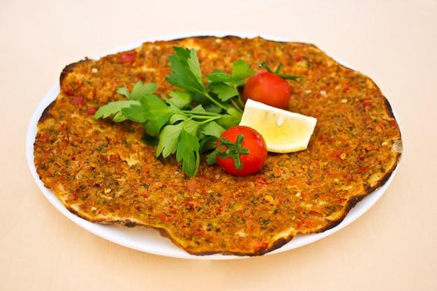 Turkse tortilla pita met gehakt en kruiden, met cherrytomaatjes en peterselie bladeren.