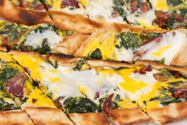 Turkse tortilla pita met spekweefsel, eieren en groene kruiden.