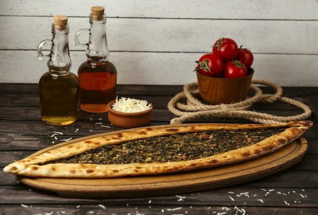 Turkse traditionele pide met gevulde vlees en kruiden op een houten bord
