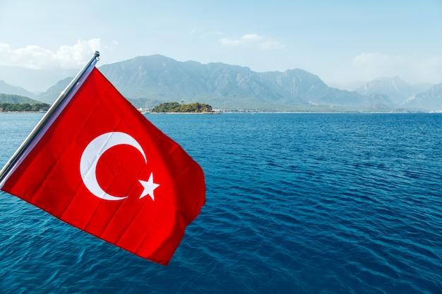 Turkse vlag die in de wind tegen de achtergrond van het overzees en de kust vliegen