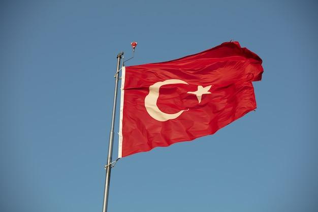 Turkse vlag met rode en witte maan in blauwe lucht