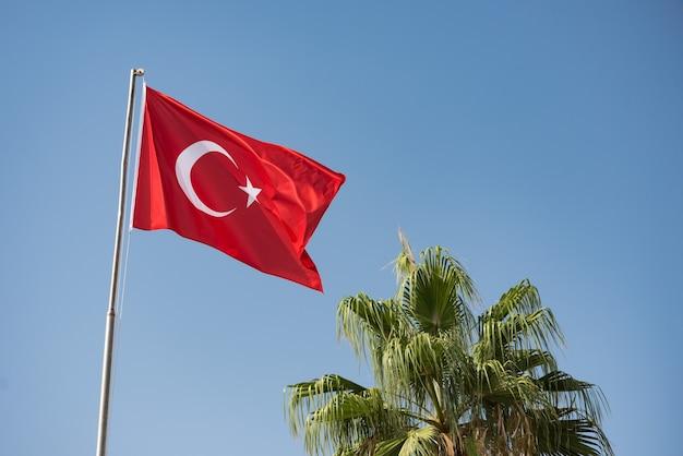Turkse vlag zwaaien in de wind tegen de blauwe lucht