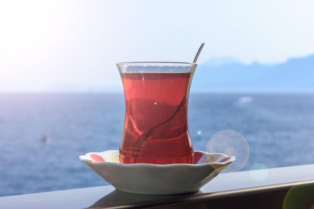 Turkse zwarte thee in traditioneel glas op achtergrond van blauwe middellandse zee