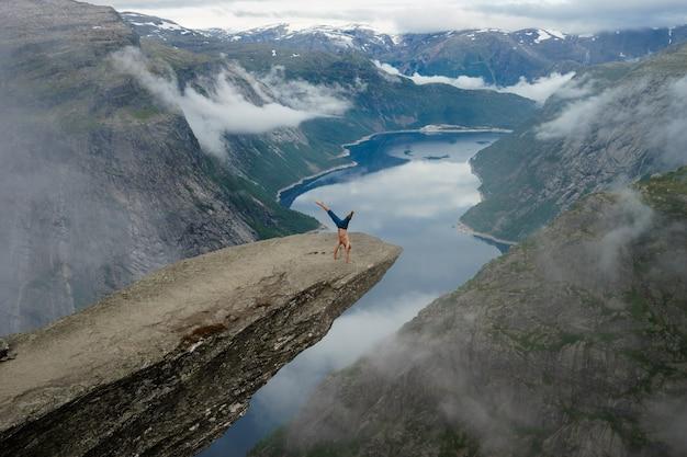 Turnster die zich op zijn handen op de rand met fjord op oppervlakte dichtbij trolltunga bevindt