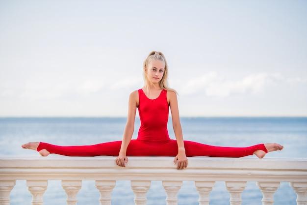 Turnster tienermeisje in een rood pak poseren op de dijk tegen de achtergrond van de zee en de lucht
