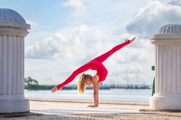 Turnster tienermeisje in rood pak poseren op dijk tegen de achtergrond van de zee en de lucht