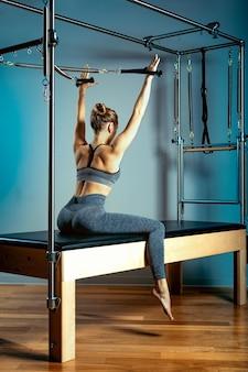 Turnster vrouw pilates stretching sport in hervormer bed instructeur meisje. blauwe achtergrond, gezond lichaam, stretching gymnastiek. geschiktheidsconcept.