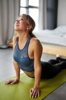 Turnster vrouw spieren uitrekken, sporten flexibiliteit oefeningen thuis doen, het dragen van sportkleding. vrouw leidt een gezonde levensstijl