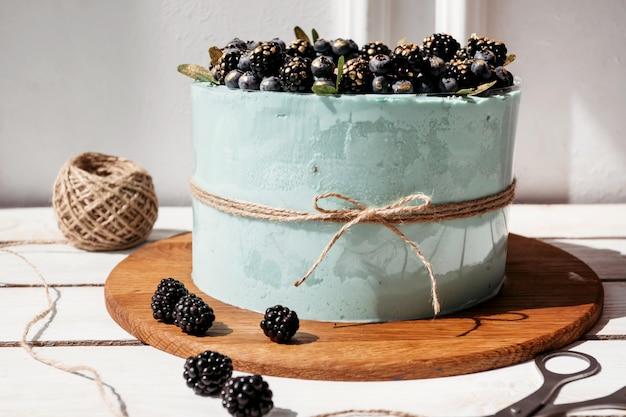 Turquoise cream cake met bosbessen en bramen, stilleven thuis bakken, business
