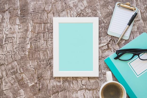 Turquoise fotolijst; koffiekop; brillen en klembord met pen op achtergrond