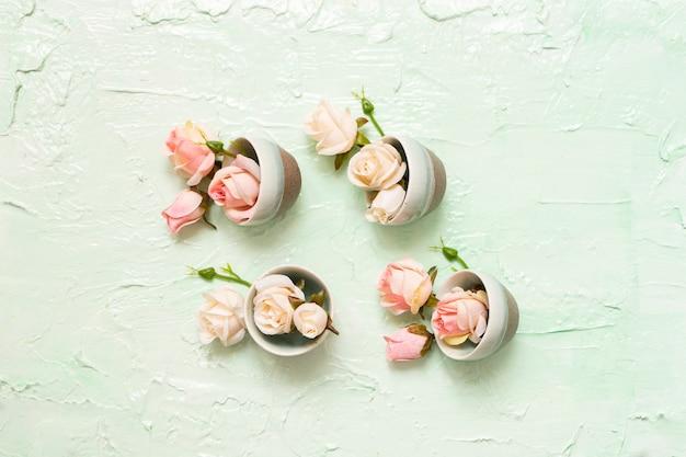 Turquoise kopjes met roze rozenbloesems op mint