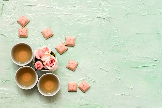Turquoise kopjes met rozenthee, rozenbloesems, roze chocolade op neomunt