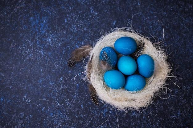 Turquoise paaseieren met twijgen in een decoratief nest op blauw
