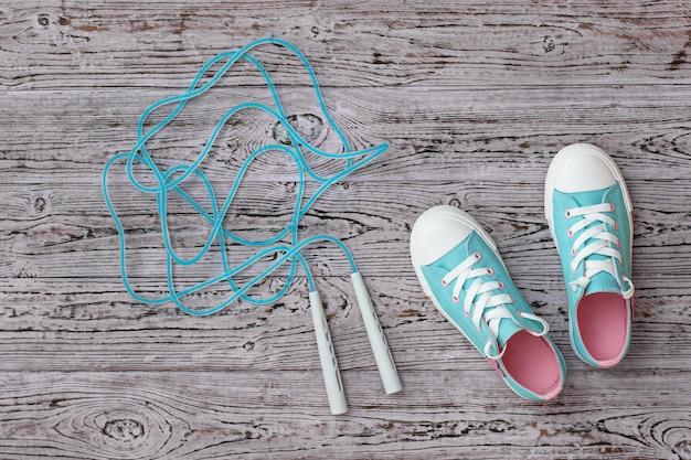Turquoise sneakers en een hoge snelheid springtouw op de houten vloer