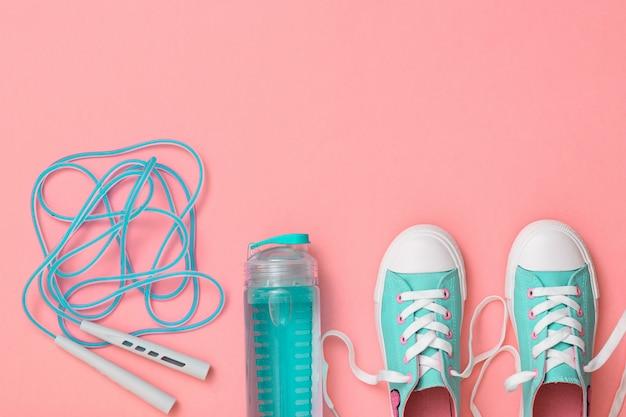 Turquoise sneakers en een springtouw met hoge snelheid op roze