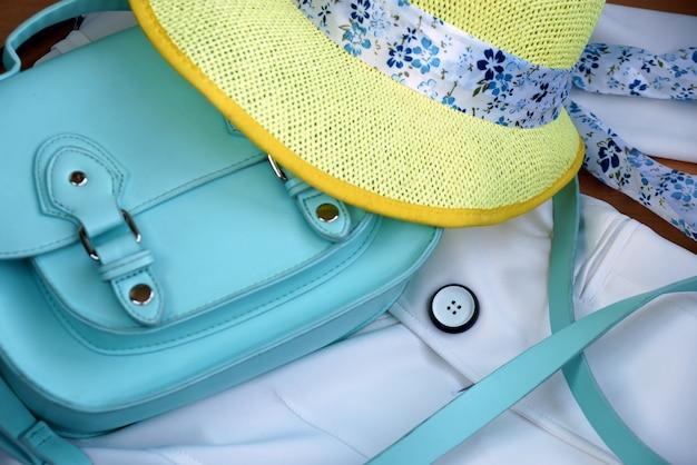 Turquoise tas voor dames en gele hoed op een witte jas