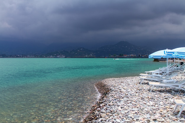 Turquoise zee en kiezelstrand met parasols en ligstoelen tegen bergen. vakantie aan zee