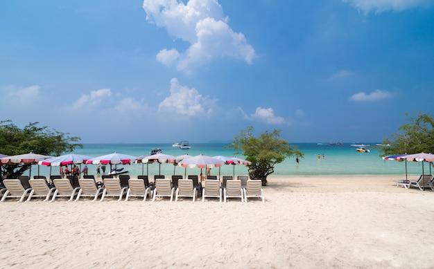 Turquoise zee, ligstoelen, wit zand en palmen