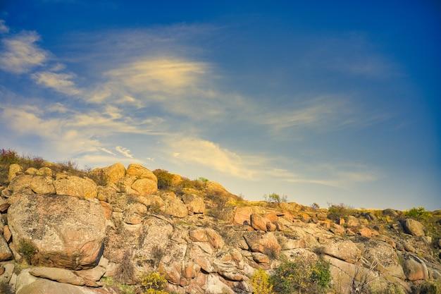 Tussen de grote rotsblokken stroomt een glad glanzende stroom in het warme avondlicht in het pittoreske oekraïne.