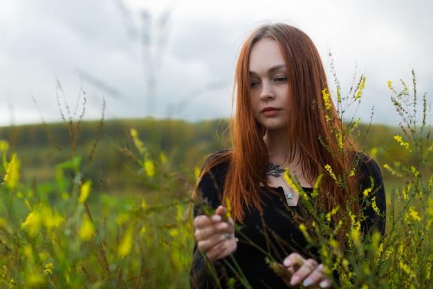 Tussen de wilde bloemen staat een peinzend roodharig meisje met een droevig gezicht