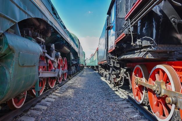 Tussen wagons van oude treinen tussen twee oude treinen rode metalen treinwielen