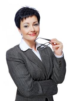 Tussentijdse volwassen zakenvrouw in grijs pak met een bril in de hand