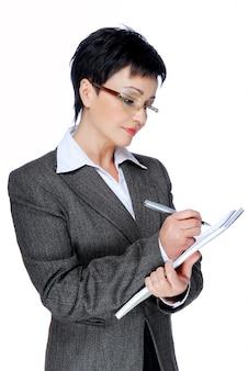 Tussentijdse volwassen zakenvrouw in grijs pak schrijven