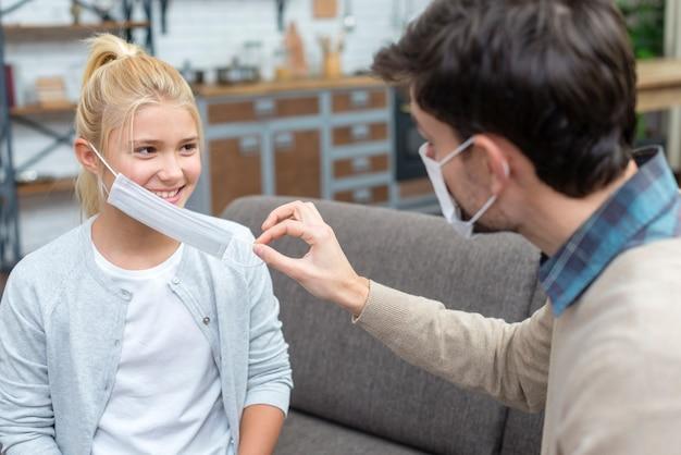 Tutor die het meisje leert hoe het masker vast te houden