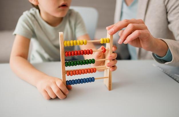 Tutor die kind leert hoe een telraam te gebruiken