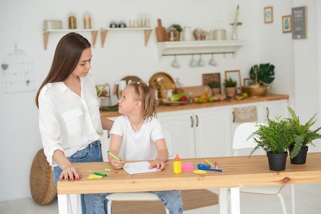 Tutor en kind huiswerk in de keuken. moeder en dochter proberen de taak op te lossen. ze zijn in een goed humeur en glimlachen.