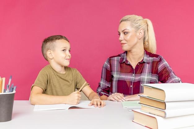 Tutor met kind huiswerk samen in de roze kamer.