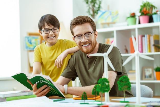 Tutorial lezen. vrolijke nieuwsgierige leraar die zijn studentenmogelijkheden van windmolens uitlegt terwijl hij een plastic model ontdekt