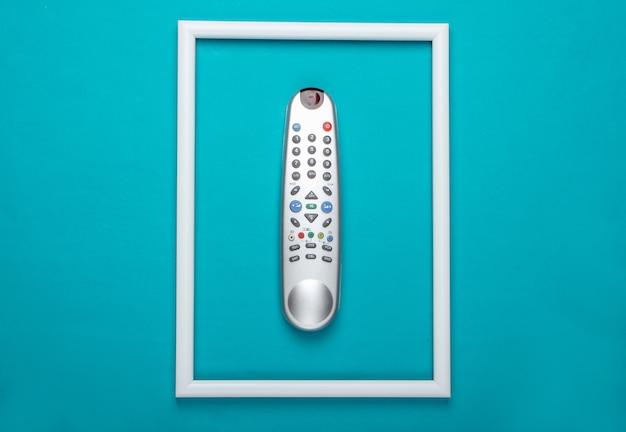 Tv-afstandsbediening op blauw oppervlak met wit frame