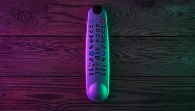 Tv-afstandsbediening op houten oppervlak met groen en magenta neonlicht